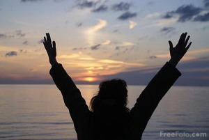 Picture of hands held high in worship at sunset.